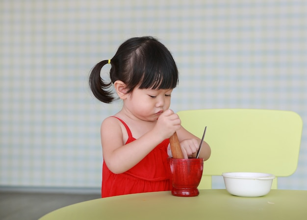 アジアの子供の女の子がグリーンパパイヤサラダを作る