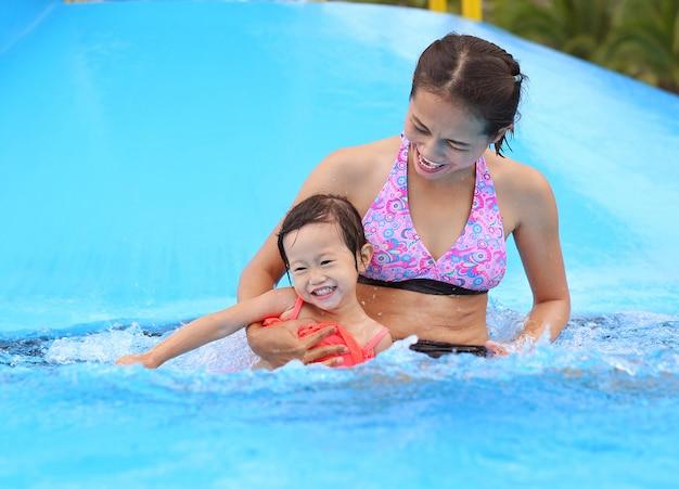 屋外スイミングプールで遊んで彼女の母親と一緒にかわいい女の子