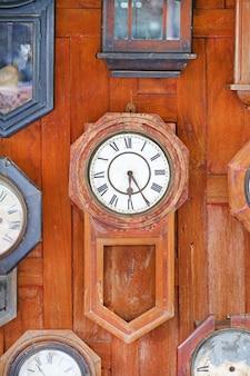 Коллекция старинных деревянных часов на фоне деревянной стены