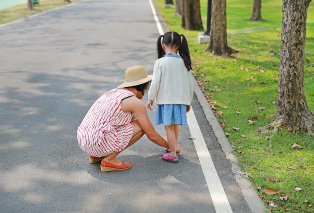 アジアの母親が彼女の小さな娘が屋外の道に靴を履くのを手伝っています。