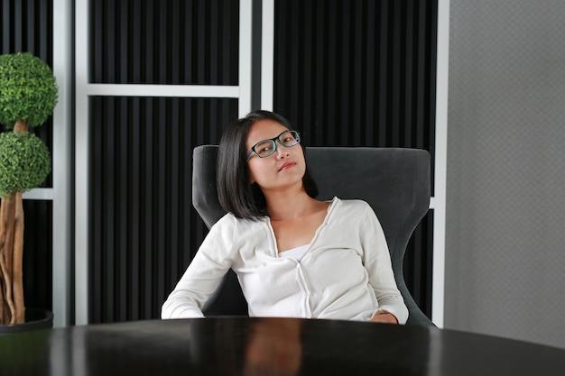 アジアの女性はリラックスして図書館で横になっています。