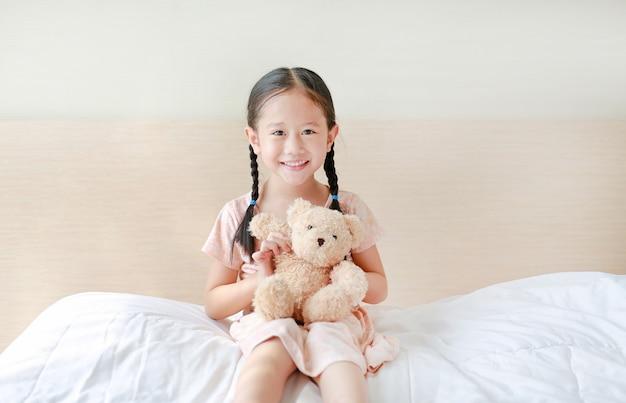 愛らしい小さなアジアの女の子が自宅のベッドの上に座っている間テディベアを遊んで