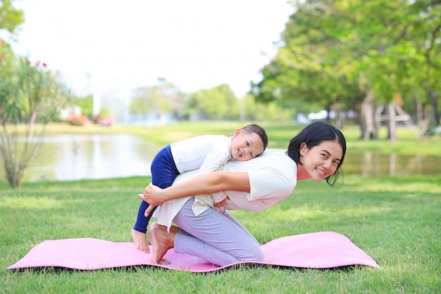 Портрет азиатской матери, делая упражнения для своего сына на зеленой лужайке в саду природы открытый