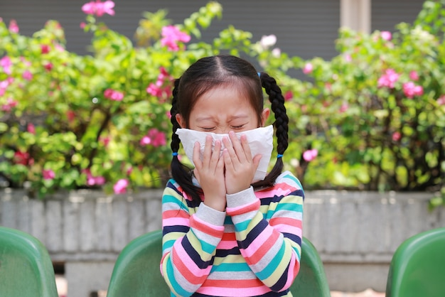 屋外の間にティッシュペーパーで鼻にくしゃみをする少女
