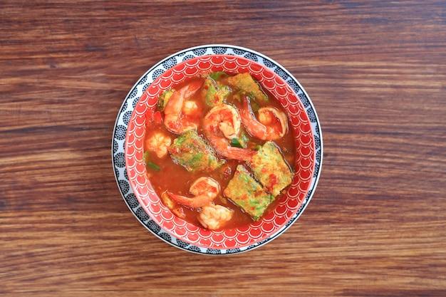 Вкусный тайский желтый карри с креветками и жареным омлетом из овощей в миске
