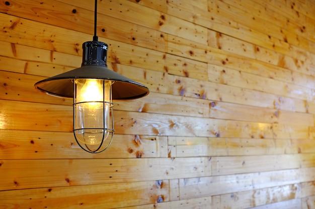 木製の壁にぶら下がっているビンテージスタイルランプの装飾。