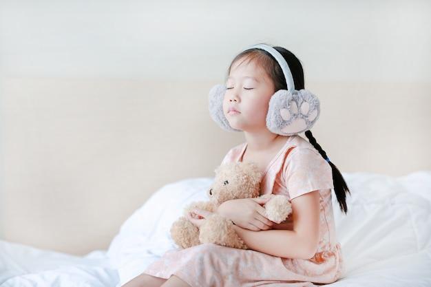 目を閉じて冬のイヤーマフを着て、自宅のベッドに座っている間テディベアを抱きしめる少女。