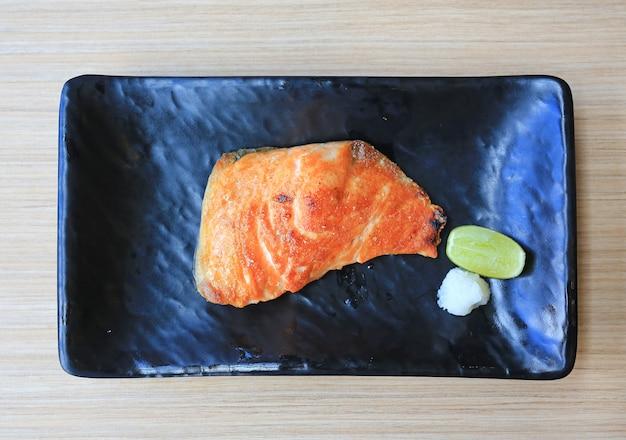 Стейк из филе лосося с солью на черном подносе. японская кухня.