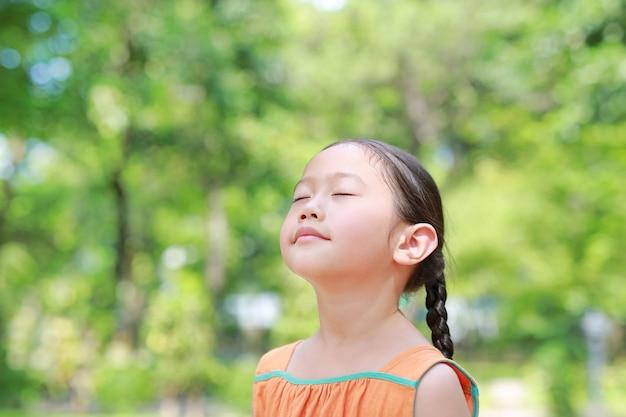 幸せなアジアの子供の肖像画は、自然からの新鮮な空気を吸うと庭で彼らの目を閉じます。