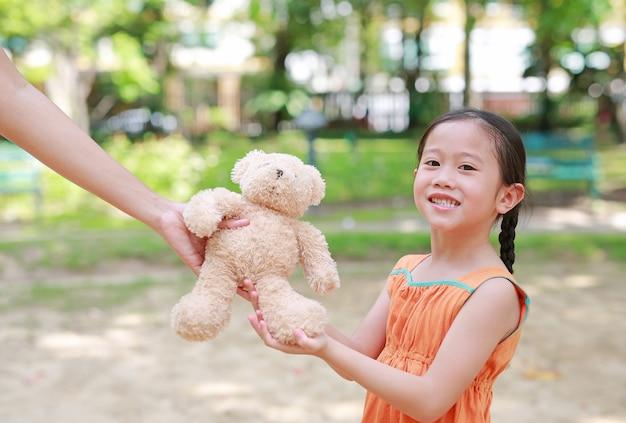 母は屋外の公園で彼女の娘のためにテディベア人形をします。女の子のためのお母さんからの贈り物。