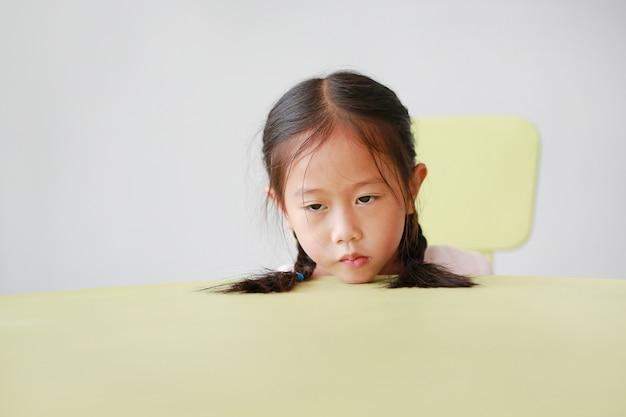 眠そうな小さなアジア子供女の子は教室のテーブルに頭を置きます。