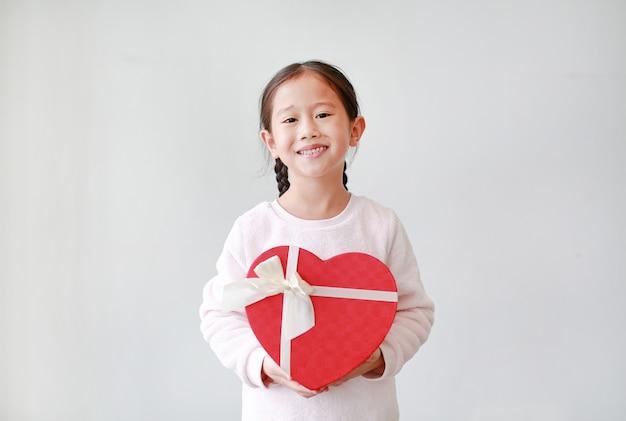 アジアの女の子は白で隔離赤いハートギフトボックスを保持しています。