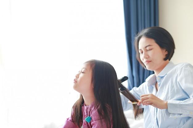 長い髪とお母さんと美しい小さなアジアの子供の女の子は、部屋で朝の滑らかな髪のドレスアップ。
