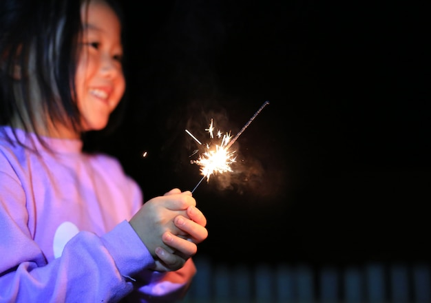 アジアの小さな子供の女の子は爆竹を楽しむ