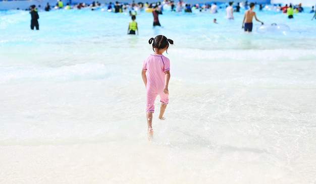 楽しんで、休日にアクア公園に実行している小さなアジアの子女の子。背面図の子供は屋外の大きなスイミングプールで楽しんでいます。