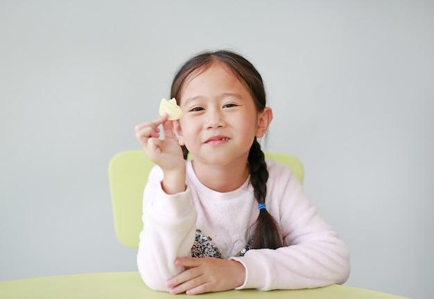白い背景の上にシャキッとしたポテトチップスを食べる小さなアジアの子少女の笑顔。子供は食べるコンセプトをお楽しみください。