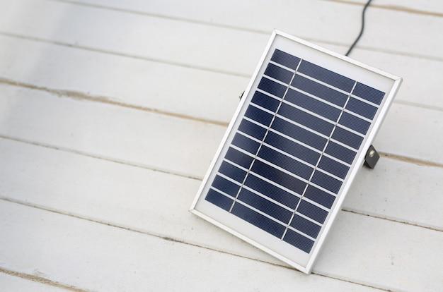 白い木製の背景に太陽電池パネル。