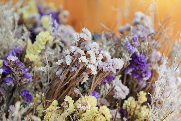 黄色の背景のカフェで色の花の装飾を乾燥させます。中央にセレクティブフォーカス。