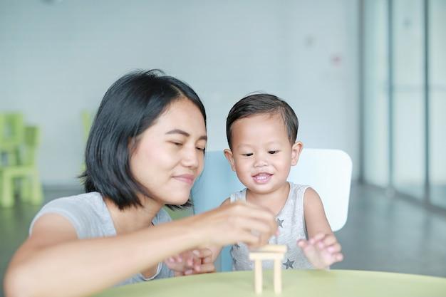 幸せなアジアのお母さんと木製のブロックを遊んでいる小さな男の子は、教室で脳と身体の発達のスキルのためのゲームをタワーします。子供の顔に焦点を当てます。子供の学習と精神的スキルの概念。