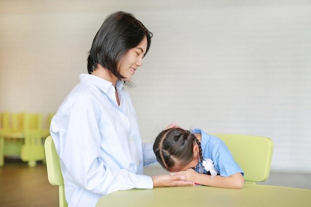 愛らしい小さなアジアの女の子は母親を尊重します。タイの母の日。