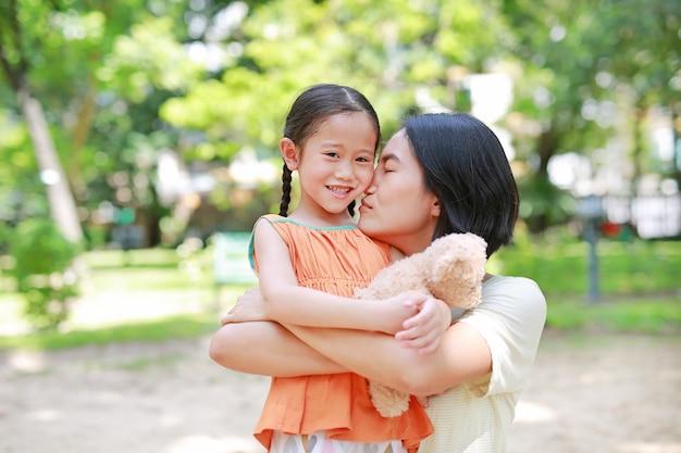 幸せなアジアの母の抱擁娘と庭でハグテディベア人形の肖像画。