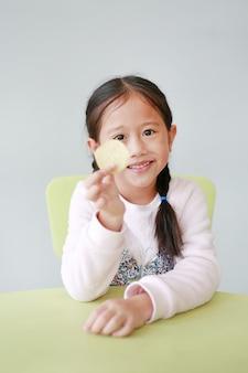 白のシャキッとしたポテトチップスを食べる小さなアジアの子少女の笑顔。
