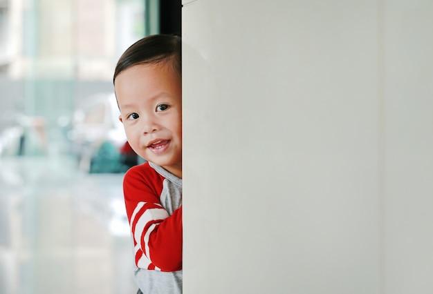 笑顔の小さなアジアの男の子が角部屋の後ろに隠れます