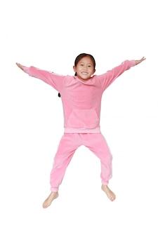 空気中のジャンプピンクのスポーツ布で面白い小さなアジアの子女の子