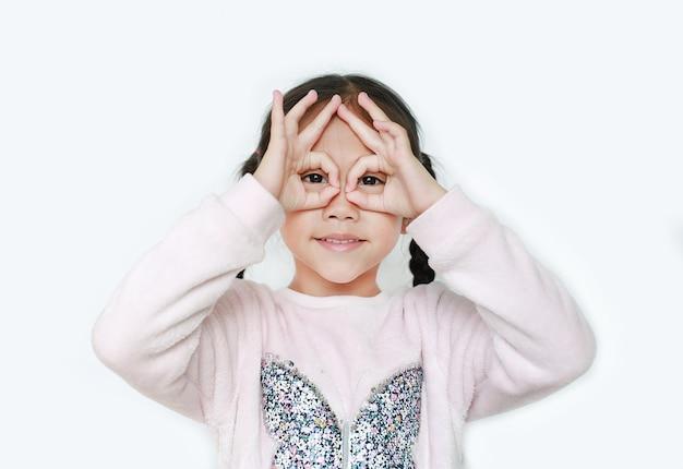 彼女の目の前で手眼鏡を持つ子供