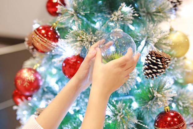 Закройте вверх по рукам ребенк украшая рождественскую елку в сезоне зимы и с новым годом.