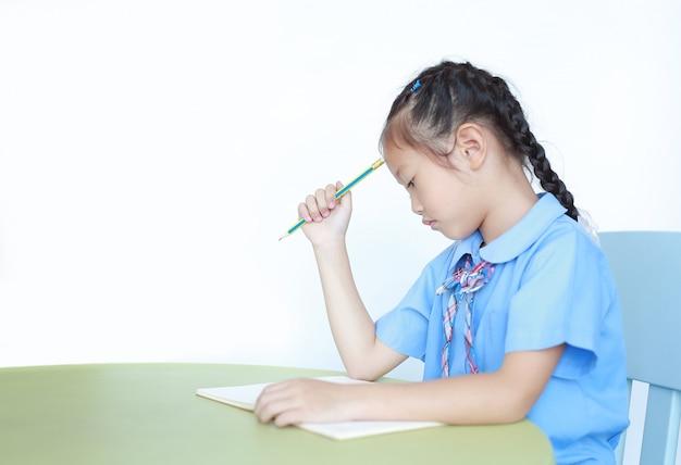 Усиленная маленькая девочка в школьной форме сидя на изолированном столе. школьница несчастной делает домашнее задание. ученик усердно и устало изучает книгу за столом.
