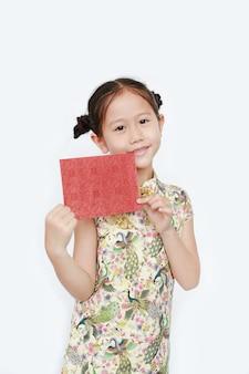 笑顔と赤い封筒を保持しているチャイナドレスを着て幸せな小さなアジアの女の子の肖像画。旧正月おめでとう。
