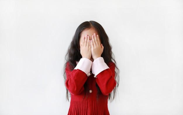 Маленькие азиатские глаза заволакивания девушки ребенка при изолированные руки.