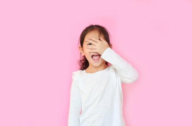 Маленькая девочка закрыла лицо руками и глаза на розовом фоне