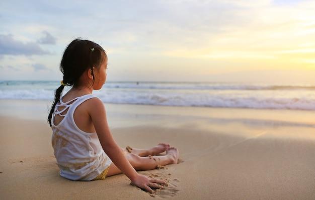 アジアの女の子、座って、砂浜のビーチで夕暮れに遊んでいる。