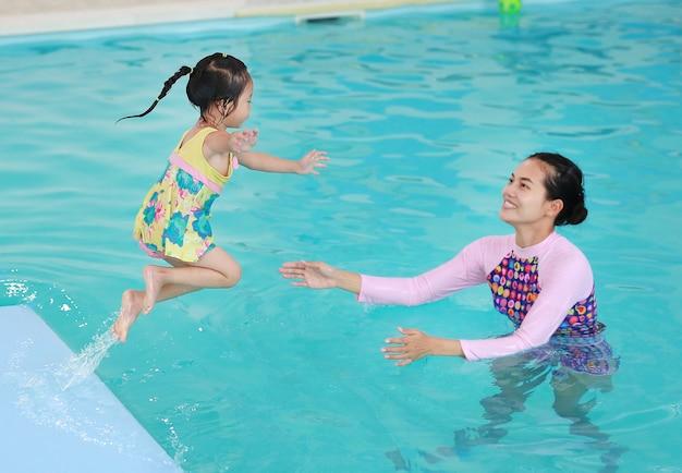 Семья матери учит ребенка в бассейне