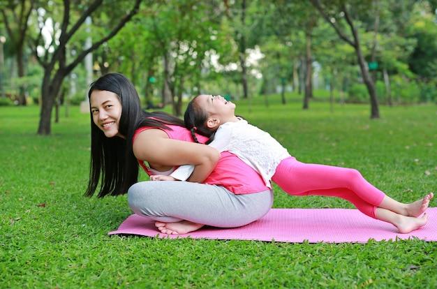 幸せな母親と彼女の娘は公園で運動しています。