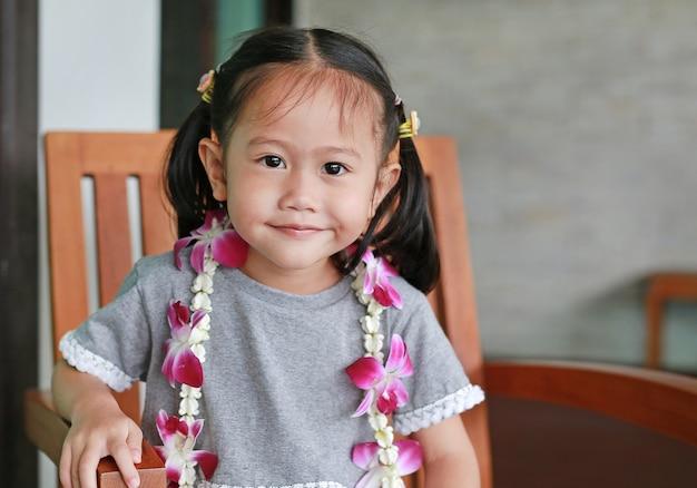 歓迎蘭の花の花輪と笑顔小さなアジアの女の子の肖像