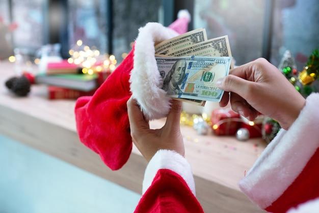 サンタクロースの手は、クリスマスの装飾に対してサンタ靴下とドル紙幣を保持