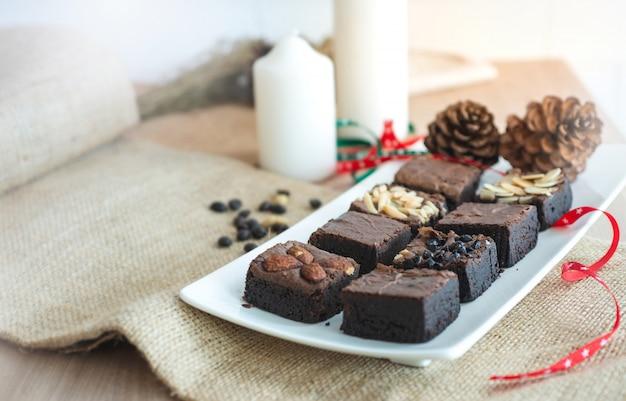 クリスマスの装飾の背景で、白いプレートにブラウニーチョコレートケーキ