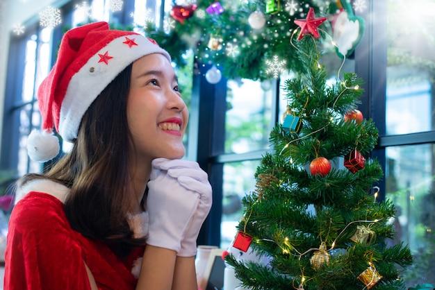 クリスマスの服を着た美しいアジアの女の子、クリスマスのために祈るサンタの帽子クリスマスコンセプト