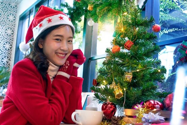 クリスマスツリーと贈り物、クリスマスの雰囲気に満足しているサンタの帽子と赤いコートで幸せな女の子