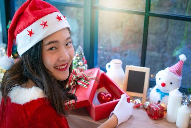 美しいアジアの女の子、クリスマスを着て、サンタの帽子、開いたギフトボックス、赤い心のボックス