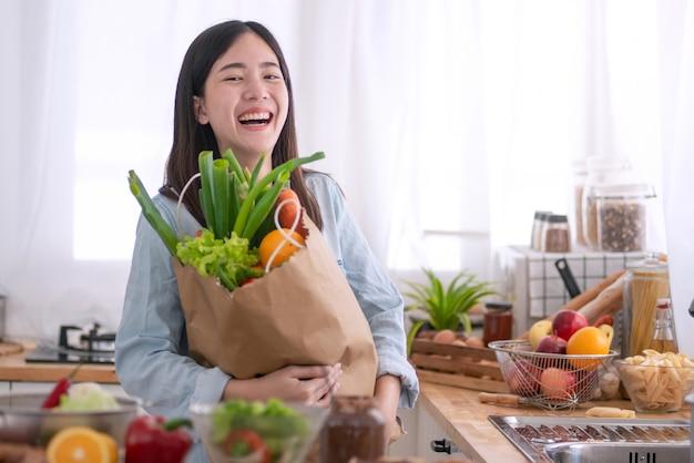 キッチンで、食料品の買い物袋を持つ若いアジア人女性