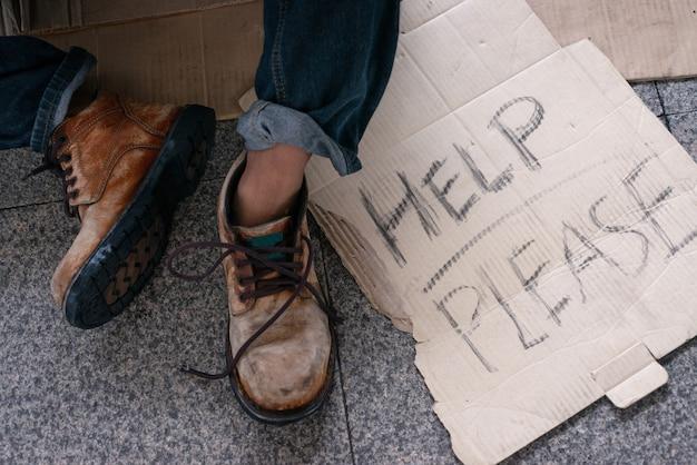 段ボールのテキストを持つホームレスの人々の靴