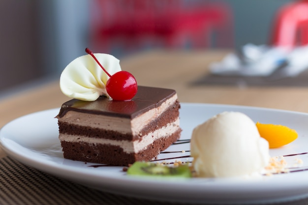 チョコレートレイヤーケーキとバニラアイスクリーム、新鮮なフルーツとチェリー