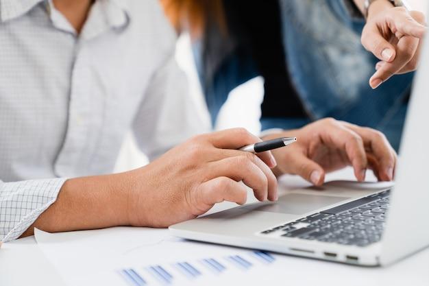 カジュアルなビジネスマンおよびオフィスでラップトップコンピューター上のビジネスを議論するチーム会議