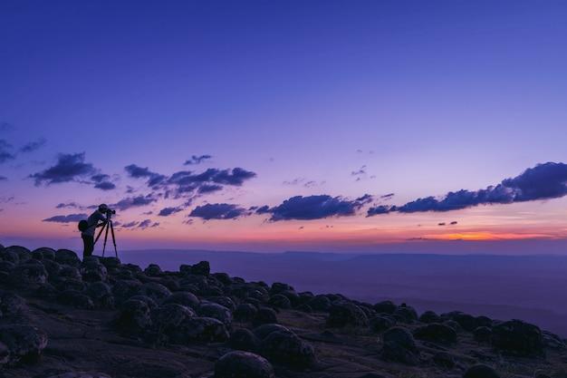 Фотограф, фотографирующий красивый пейзажный закат в национальном парке фу хин ронг кла