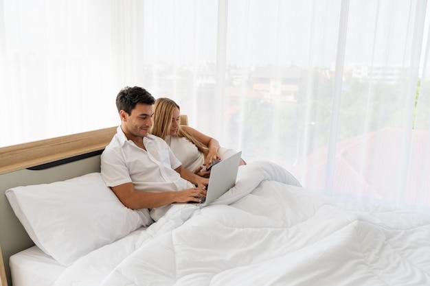 早朝の寝室で一緒にノートパソコンとスマートフォンでソーシャルメディアと一緒に楽しんでいるカップルの白人の恋人