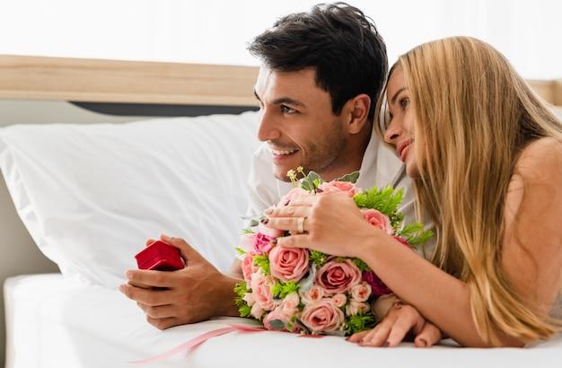 結婚指輪の箱を手で押しながらベッドの上の恋人と幸せな笑顔のカップル